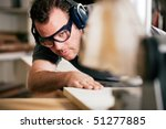 Carpenter working on an electric buzz saw cutting some boards, he is wearing safety glasses and hearing protection to make things safe - stock photo