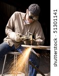 Stock photo a man using his torch cutter to cut through some metal with sparks flying onto the ground 51301141