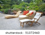 An array of modern wicker garden furniture on a patio in the home garden. - stock photo
