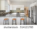 Stock photo modern kitchen in white with bar stools and grey counter top 514121785