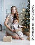 Small photo of Portrait of happy mother and adorable baby celebrate Christmas. New Year's holidays. Toddler with mom in the festively decorated room with Christmas tree and decorations.