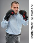 Small photo of Studio portrait of an aggressive businessman with boxing gloves punching