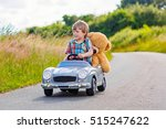 Stock photo little preschool kid boy driving big toy car and having fun with playing with his plush toy bear 515247622