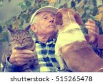 Stock photo senior man enjoying tender moments with his cat and dog cuddling them in courtyard 515265478