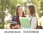 Stock photo two happy students walking and talking each other in a campus at sunset with a warm light 515324818