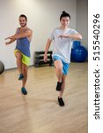 Small photo of Portrait of two men doing aerobic exercise in fitness studio