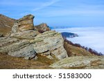 Rocks in mountains over clouds - stock photo