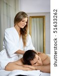 The girl does massage to the patient in spa salon - stock photo