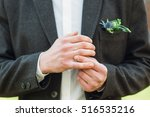 Small photo of Groom fit on his wedding ring on right hand. Close-up of man in suit hands fidgeting golden wedding ring