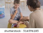 sad young boy sitting on a pouf ... | Shutterstock . vector #516596185