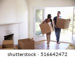 couple carrying boxes into new... | Shutterstock . vector #516642472