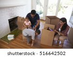 family unpacking boxes in new... | Shutterstock . vector #516642502