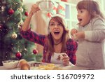 Small photo of Mother and daughter making Christmas cookies and having fun. Mother sifts the flour through a sieve on the great amazement of her daughter
