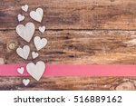 Small photo of Valentine´s Day Love Hearts background on rustic wood with red checkered ribbon