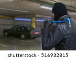 Thief with crowbar is going to steal car from garage. - stock photo