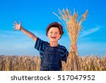 happy farmer's boy with sheaf... | Shutterstock . vector #517047952