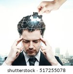 Stock photo hand adding last piece to pensive puzzle headed businessman on city background business challenge 517255078