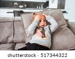 pretty baby on sofa. hends on... | Shutterstock . vector #517344322