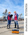 Small photo of Two workers in the oilfield, one holding the radio second showing papers. Pump jack and wellhead background. Oil and gas concept.