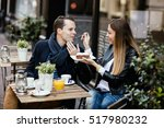 Small photo of Lovely couple eating together a piece of cake. Girl feeding her boyfriend. Sharing is caring. Noise added, selective focus