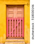 Small photo of Multicolored adobe building and wooden door with picket gate in Cozumel, Mexico