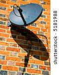Satellite dish with its shadow on the supporting wall - stock photo