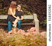 Small photo of Love romance flirt dating concept. Affectionate couple sitting on bench. Young girl sitting on her boy lap.