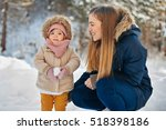 mother and baby girl in a warm... | Shutterstock . vector #518398186