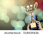 hand holding gold trophy on... | Shutterstock . vector #518434636