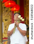 Small photo of PHUKET TOWN, THAILAND, OCTOBER 05, 2016 : A man is praying, holding lotus flowers and incense sticks in the Sapha Hin Shrine of Phuket Town, Thailand