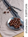 Small photo of A metal nutcracker and a vintage pewter plate with whole hazelnuts. Rustic linen kitchen towel.