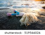 Small photo of Baby doll,Abandoned doll laying on a floor in the beach,Abandon concept