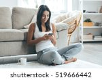 Lovely message from him. Attractive young woman looking at her smart phone and smiling while sitting on the carpet at home
