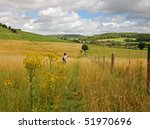 Small photo of Lady Hiker looking through binoculars over an English Rural Landscape with Hamlet