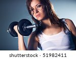 Young strong sexy woman with dumbbell. Camera angle view. - stock photo