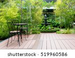 Small photo of Black chair in wood patio at green garden with fountain in house. Outdoor garden.