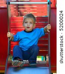 Kid on a slide (with a step forward) - stock photo