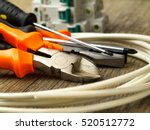Small photo of set of electrician tools, a coil of wire and switches in background, focus on cutter