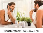 happy guy using electric razor   Shutterstock . vector #520567678