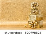 Gifts With Ribbon Bow On Golde...