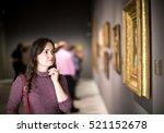 Stock photo portrait of positive young girl attentively looking at paintings in art museum 521152678