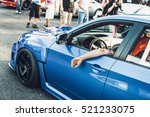 man sits in blue bmw on the...   Shutterstock . vector #521233075