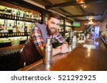 Stock photo portrait of cheerful young bartender standing and smiling in bar 521292925