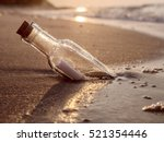 Small photo of Message in the bottle washed ashore against the Sun setting down