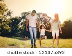 playful family outdoors walking ... | Shutterstock . vector #521375392