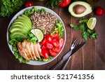 Healthy salad bowl with quinoa, tomatoes, chicken, avocado, lime and mixed greens, lettuce, parsley on wooden background top view. Food and health.