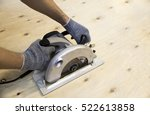 Men's gloved hands working with a circular saw - stock photo