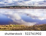 Stock photo alone fishermen fishing in a big lake in autumn on cloudy day 522761902