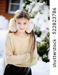 Small photo of Funny adorable little girl in gold sweater and fur headphones having fun in beautiful winter park