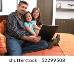 Father and children lying on the bed at home and looking into a portable computer - stock photo